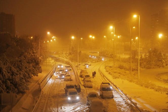 Des automobilistes abandonnent leurs véhicules immobilisés sur une bretelle d'accès à l'autoroute M-30, proche de Madrid, dans la nuit du 8au 9janvier 2021.