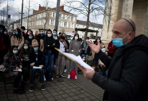 "Nantes' university teacher Olivier Ertzscheid gives a lecture in a square outside a church in la Roche-sur-Yon, western France, on December 15, 2020, to raise awareness on the ""deap psychological distress of students"" as French government decide to remain universities closed as a measure to curb the spread of the Covid-19 pandemic whereas churches and other cult places are allowed to open. / AFP / LOIC VENANCE"