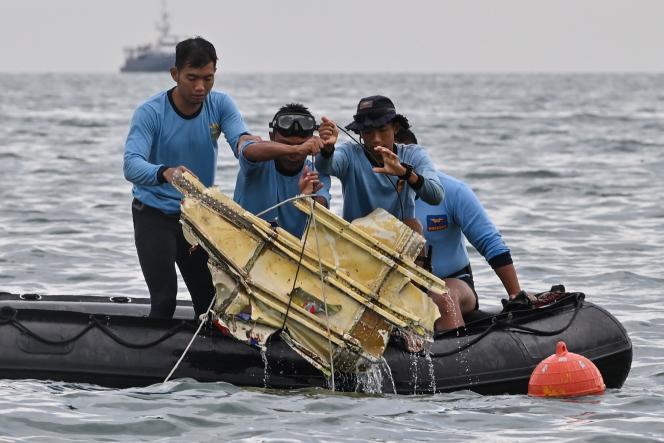 Des plongeurs de la marine indonésienne retrouvent une pièce du vol SJ182, près del'île de Lancang, le 10 janvier.