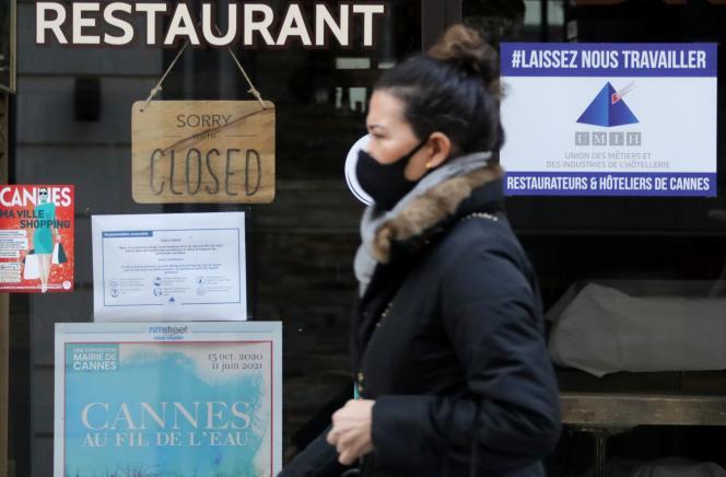 Une femme masquée passe devant un restaurant fermé à Cannes, en janvier 2021.