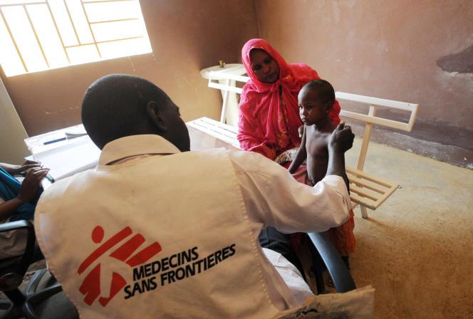 Un membre de Médecins sans frontières (MSF) avec un enfant malade et sa mère à Gao, dans le nord du Mali, en 2013.