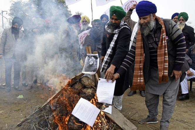 Farmers burn copies of recent agricultural reforms and a photo of Indian Prime Minister Narendra Modi in Amritsar on January 9.