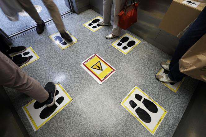 Social distancing pictograms in an elevator in Tokyo, September 28, 2020.