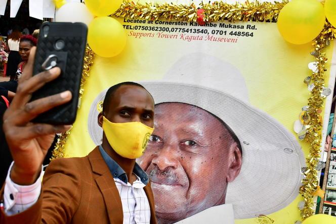 Un soutien du président ougandais Yoweri Musevini se prend en photo devant une de ses affiches de campagne, le 12 janvier à Kampala.
