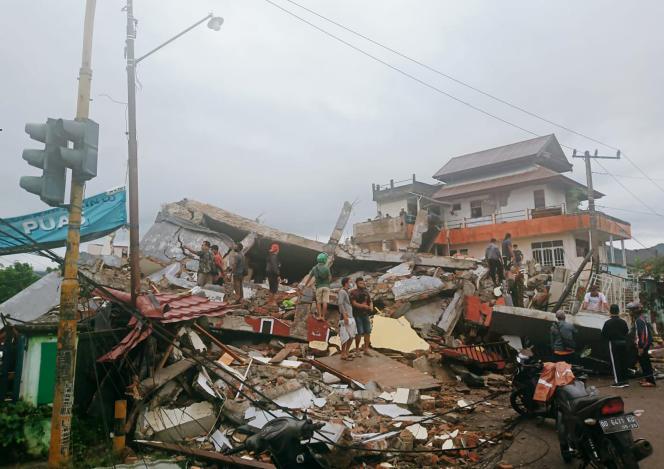 Warga menyelidiki bangunan yang rusak akibat gempa di Mamuju, Pulau Celebes, Indonesia, pada Jumat 15 Januari.