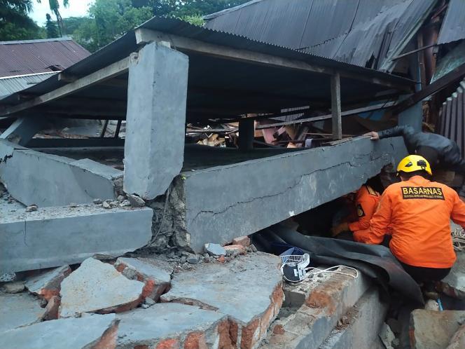 Tim penyelamat mencari korban di sebuah bangunan yang runtuh di Mamuju, Pulau Celebes, Indonesia, pada 15 Januari.