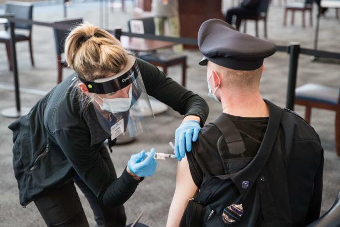 یک افسر پلیس 15 ژانویه واکسن Covid-19 خود را در سایت واکسیناسیون استادیوم ژیلت در فاکسبورو ، ماساچوست دریافت کرد.