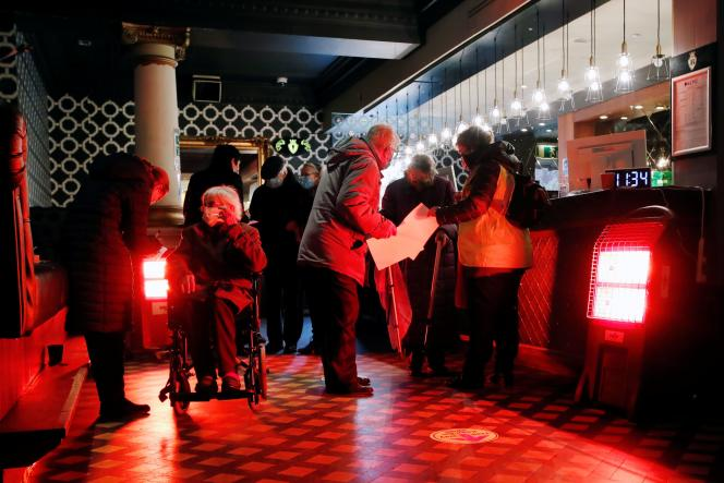 Des personnes attendent de recevoir le vaccin dans un night club transformé en centre de vaccination, le 15 janvier, à St Albans, en Angleterre.