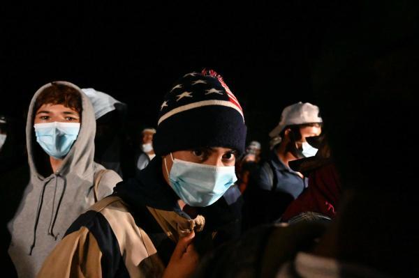 Les migrants marchent en colonne le long des routes, sac au dos, la plupart le visage couvert d'un masque en raison de la pandémie de Covid-19.