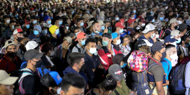 Thousands of Honduran migrants push through the police fence as they attempt to cross the border at El Florido in Guatemala forming the first migrant caravan of the year on it's way to the United States on January 15, 2021. Some 3,000 people left Honduras on foot January 15 in the latest migrant caravan hoping to find a welcome, and a better life, in the US under President-elect Joe Biden. Seeking to escape poverty, unemployment, gang and drug violence and the aftermath of two devastating hurricanes, the migrants plan to walk thousands of kilometers through Central America.  / AFP / Johan ORDONEZ