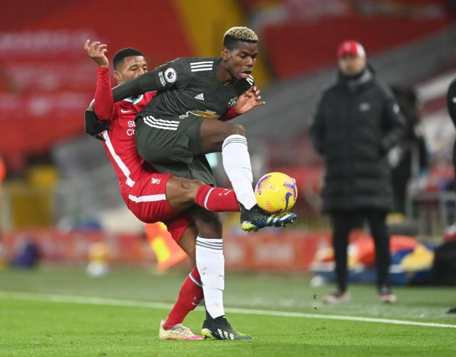 Paul Pogba protège la balle contre Georginio Wijnaldum lors du match à Liverpool.