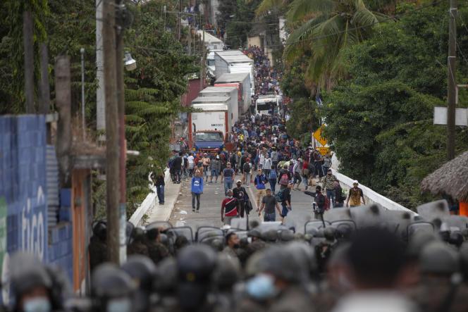 Des migrants honduriens face à des soldats et policiers guatémaltèques qui tiennent un barrage routier les empêchant d'avancer vers les Etats-Unis, sur l'autoroute, à Vado Hondo, au Guatemala, le 18 janvier 2021.