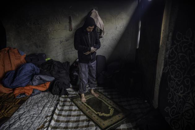 Un migrant afghan prie dans une ancienne usine métallurgique abandonnée qui sert d'abri à plus d'une centaine de migrants, le 14 janvier.