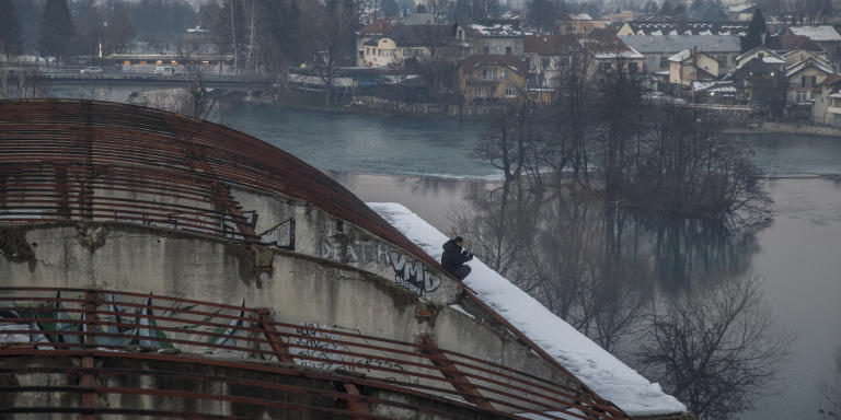 A man from Afghanistan speaks on the phone while sitting on the roof of an abandoned and destroyed building that serves as a shelter to over one hundred migrants as temperature drops to -10C in Bihac, January 14, 2021. Photo by Damir Sagolj for Le Monde