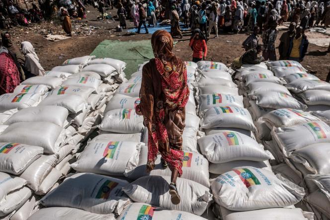Une femme marche sur des sacs de farine pendant une distribution de nourriture organisée par le gouvernement éthiopien dans la ville d'Alamata le 11 décembre 2020.