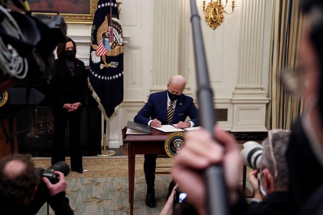 Joe Biden signe un décret sous le regard des caméras et de sa vice-présidente Kamala Harris.