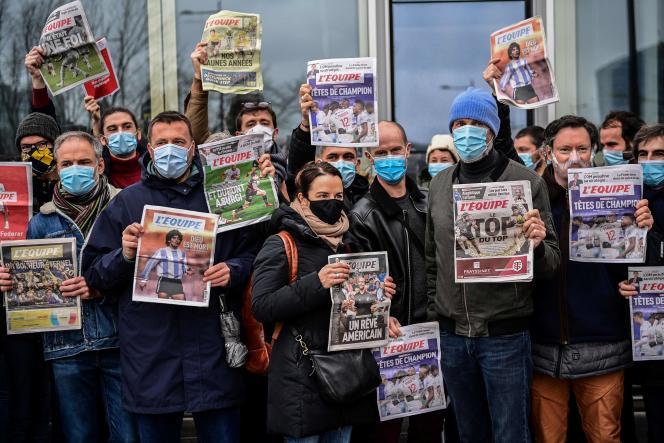 Des employés de « L'Equipe» lors d'un rassemblement devant le siègedu quotidien, à Boulogne-Billancourt (Hauts-de-Seine), près de Paris, le 13 janvier.