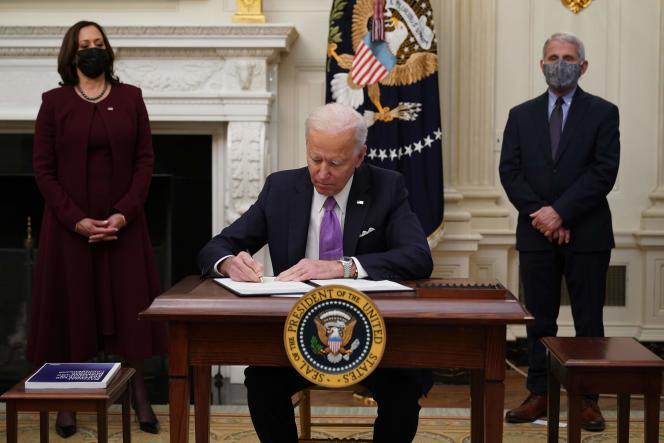 Joe Biden signe un décret à la Maison Blanche, sous les regards de sa vice-présidente, Kamala Harris, et de l'immunologueAnthony Fauci.
