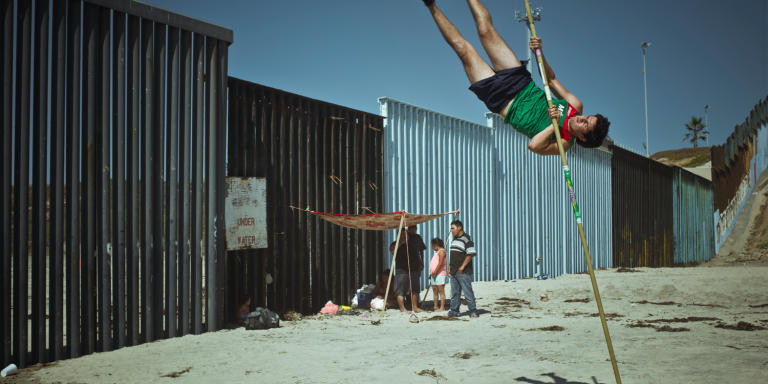 MEXICO. Tijuana. 2018. Jorge Luna, a professional Mexican pole vault jumper trains by the border fence on the beach of Tijuana.