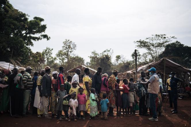 Un employé du Haut-Commissariat des Nations unies pour les réfugiés (HCR) accueille des réfugiés centrafricains à l'entrée d'un site de réfugiés à Ndu, dans la province du Bas-Uélé, en République démocratique du Congo, le 21 janvier 2021.