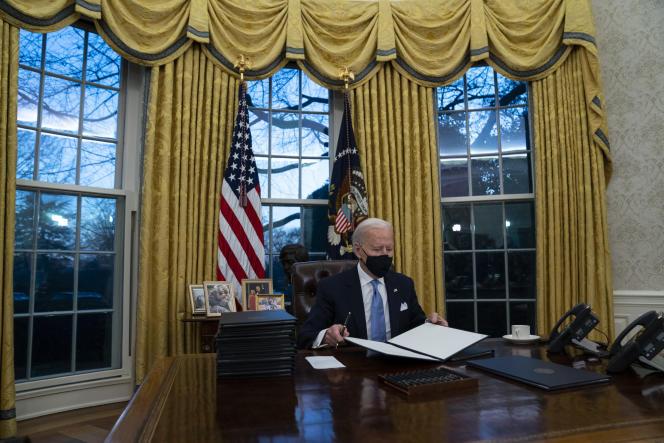 Joe Biden, nouveau président en exercice des Etats-Unis, signe ses premiers décrets dans le bureau Ovale de la Maison Blanche, le 20 janvier.
