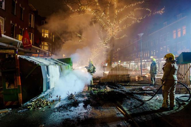 آتش نشانان پس از درگیری بین معترضین و پلیس در 25 ژانویه در روتردام ، آتش را خاموش کردند.