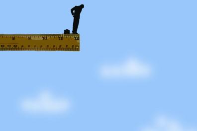 Gap between businessmen on rulers in sky