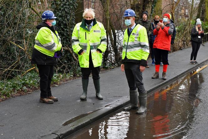 Le premier ministre britannique Boris Johnson–que l'on reconnaît à sa stupéfiante coupe de cheveux– à Manchester,le 21janvier 2021, quelques jours après les intempéries qui ont frappé la région.