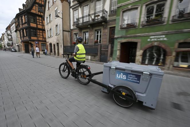 Un employé d'Urban Logistic Solutions (ULS) livre des colis en vélo électrique, à Strasbourg, en juillet 2020.
