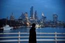 FILE PHOTO: A man looks towards skyscrapers of the City of London financial district as he crosses Waterloo Bridge, amid the coronavirus disease (COVID-19) pandemic, in London, Britain, January 15, 2021. REUTERS/Toby Melville/File Photo