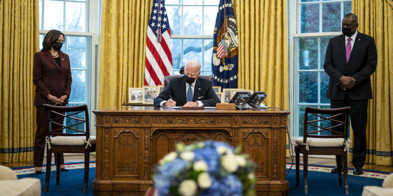 WASHINGTON, DC - JANUARY 25: Flanked by Vice President Kamala Harris (L) and Secretary of Defense Lloyd Austin (R), U.S. President Joe Biden signs an executive order in the Oval Office of the White House on January 25, 2021 in Washington, DC. President Biden signed an executive order repealing the ban on transgender people serving openly in the military.   Doug Mills-Pool/Getty Images/AFP