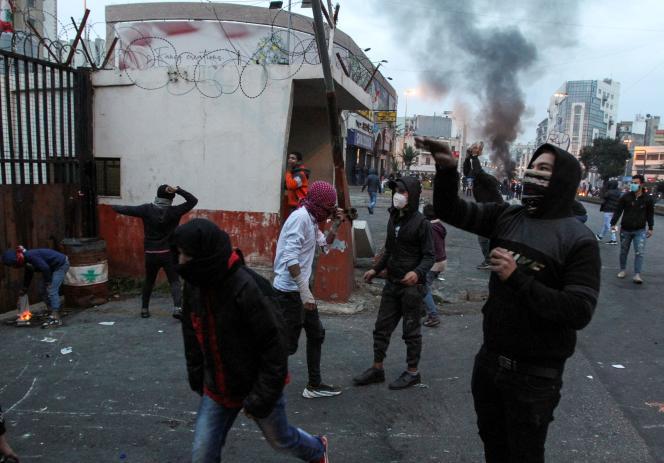 Des manifestants jettent des pierres sur un bâtiment du gouvernement, le 26 janvier à Tripoli.