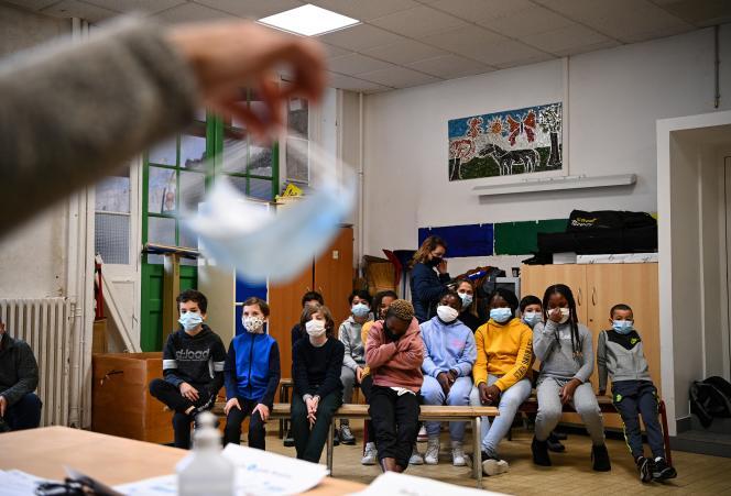 Un médecin explique à des écoliers les gestes barrières et l'équipement de protection contre le Covid-19 dans une école à Paris, le 23novembre 2020.