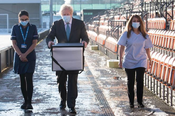 Le premier ministre britannique Boris Johnson, artisan du Brexit, porte des doses du vaccin AstraZeneca, développé en partenariat avec les chercheurs d'Oxford, à Londres, le 25 janvier 2021.