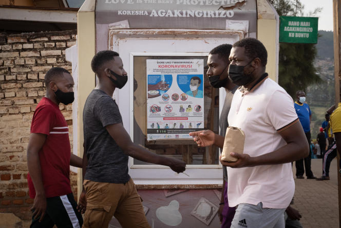 ساکنان ماسک دار در محله Nyamirambo در تاریخ 29 ژانویه 2021 از کنار پوستر پیشگیری از ویروس کرونا در کیگالی عبور می کنند.