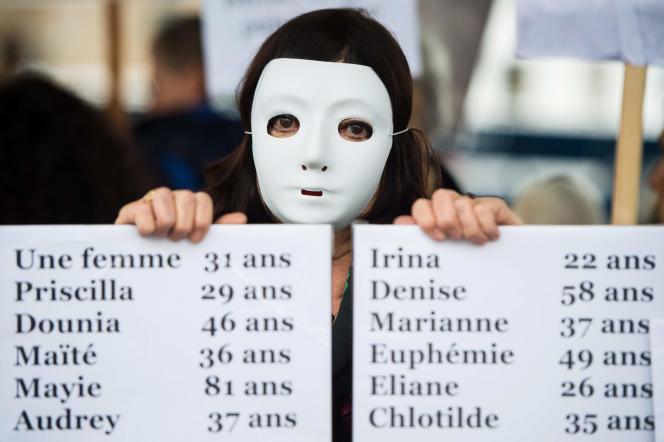 Une femme porte haut le nom des victimes de féminicides décédées depuis le début de l'année, lors d'une manifestation, à Marseille, en2019.