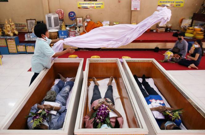 Des fidèles allongés dans des cercueils de bois simulent la position du défunt, dans un temple bouddhiste de Bangkok, le 27 janvier.