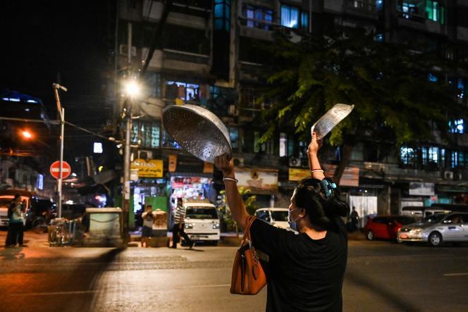 Une femme claque des casseroles pour faire du bruit, répondant aux appels à la protestation lancés sur les réseaux sociaux, à Rangoon, le 3 février 2021, après l'inculpation d'Aung San Suu Kyi.