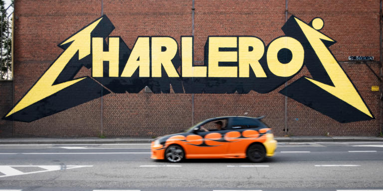 """La ville de Charleroi dans le Pays Noir, en Wallonie traîne un lourd héritage. Jadis connue pour ses mines de charbon et ses industries, elle est aujourd'hui célèbre en Belgique pour ses faits divers sordides (l'affaire Dutroux), son chômage endémique, et pour ses « barakis » (habitants des quartiers populaires). Surnommée « Chicago sur Sambre » dans les années 90 pour son fort taux de criminalité, Charleroi fut désignée en 2009 ville la plus laide du monde par un journal néerlandais...  Néanmoins, de cette ville qui tente de se réinventer, se dégagent un charme étrange et une atmosphère chaleureuse, parfois déjantée. Certains nourissent  même l' espoir d'une renaissance à la manière de Détroit aux USA.  Les carolorégiens (habitants de Charleroi), avec humour, l'appellent la """"Carolofornie"""", en """"Wallifornie""""."""