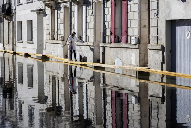 Une habitante marche sur des planches de bois dans une rue inondée de Saintes, dimanche 7 février 2021.