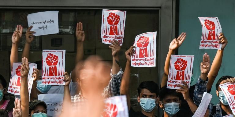 Protesters hold up the three finger salute and placards during a demonstration against the military coup in Yangon on February 7, 2021. / AFP / Ye Aung THU