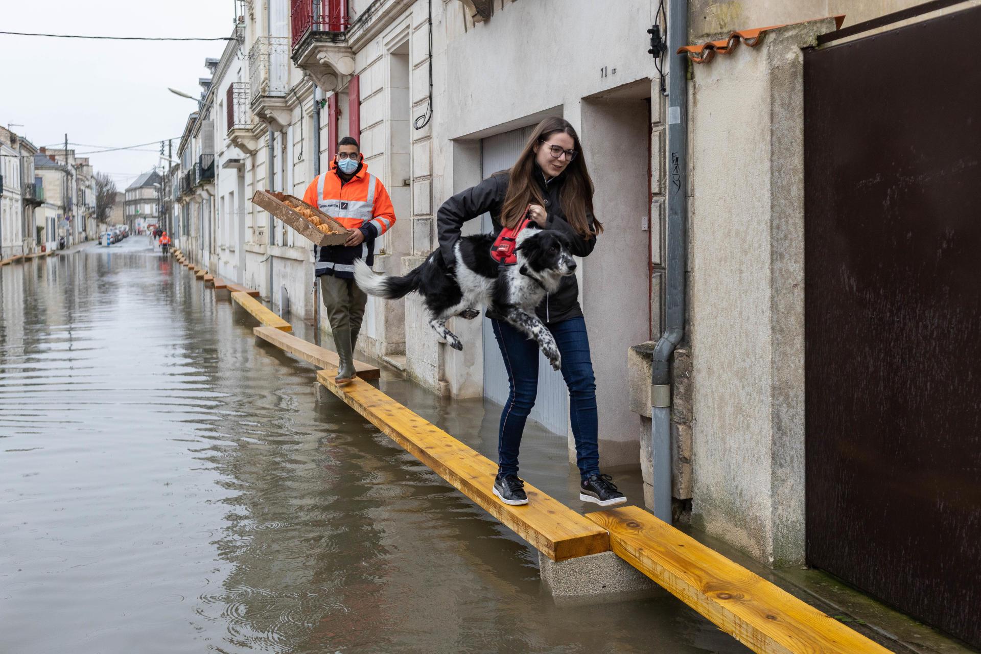 Dans les rues de Saintes, les habitants circulent sur d'étroites planches de bois posées sur des parpaings, pendant la crue de la Charente, le 8 février.