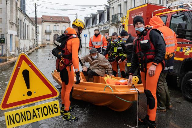 Louis Ardouin, 80ans, aidé par des pompiers et militaires pour se rendre à la pharmacie, à Saintes (Charente-Maritime), le 8 février.