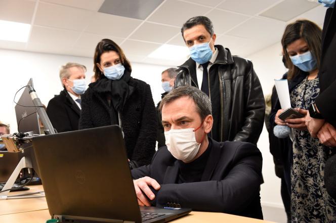 Le ministre français de la santé, Olivier Véran, accompagné du député de Moselle Belkhir Belhaddad (C), assiste à une vidéoconférence avec un expert médical de la région du Grand-Est lors de sa visite à l'agence régionale de santé (ARS) du Grand-Est à Metz, dans l'est de la France, le 12 février 2021.