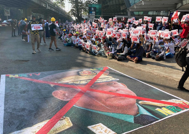 Une grande image avec une marque en X sur le visage du commandant en chef, le général Min Aung Hlaing, également président du Conseil administratif de l'Etat, se trouve sur une route alors que des manifestants anti-coup d'Etat se rassemblent devant le centre de Hledan à Rangoun, dimanche 14 février 2021.