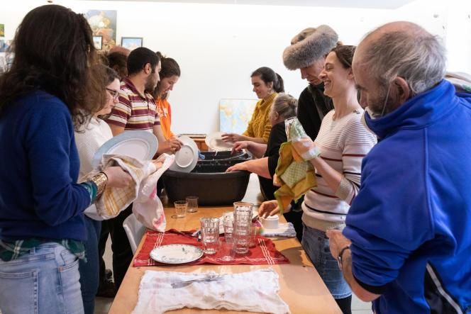 Les résidents du foyer Lazare font la vaisselle après un repas collectif.