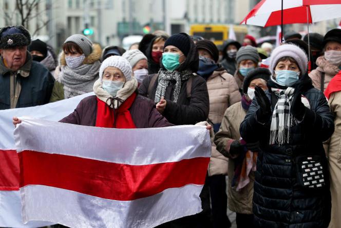 Des manifestants, en grande partie masqués, défilent dans les rues lors d'un rassemblement de protestation contre les violences policières à Minsk, le 23 novembre 2020.