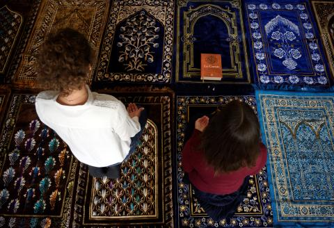 "Two female Imam, Anne-Sophie Monsinay (R) and Eva Janadin, both converted to Islam, pray in a prayer room in Paris on September 7, 2019. - An unprecedented event for Muslim worship in France: two Imam women led a prayer on September 7, 2019 in Paris, in front of a totally mixed assembly gathered for a ceremony mainly celebrated in French. Janadin and Monsinay wanted for several years to translate their vision of a ""progressive"" and ""enlightened"" Islam into concrete actions. (Photo by Lionel BONAVENTURE / AFP)"