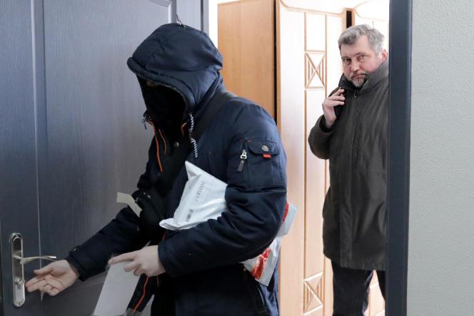 Le président de l'Association bélarussienne des journalistes (BAJ) Andreï Bastunets et des policiers biélorusses quittent le bureau de la BAJ après une descente à Minsk, le 16 février 2021.