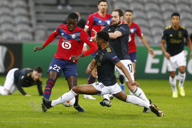 Lille's Timothy Weah, left, challenges for the ball with Ajax's Sebastien Haller, center, and Ajax's Daley Blind during the Europa League round of 32 first leg soccer match between Lille and Ajax at the Pierre Mauroy stadium in Villeneuve d'Ascq, France, Thursday, Feb. 18, 2021. (AP Photo/Michel Spingler)